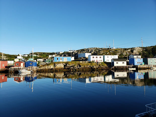Houses and fishing stages on the rocky coastline in Southwestern Newfoundland.