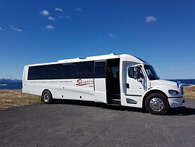 A white charter bus sits on a a paved lot.