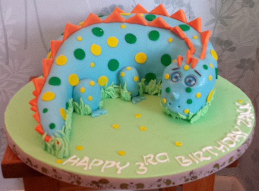 Dinosaur cake in blue with yellow and gr