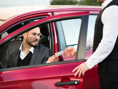 Valet Giving Receipt To Young Male Busin