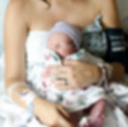 Beautiful and happy new mom holding her newborn in the hospital right after delivery at Westmoreland Hospital in Greensburg, PA