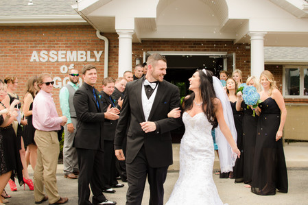 bride and grooming leaving church laughinig