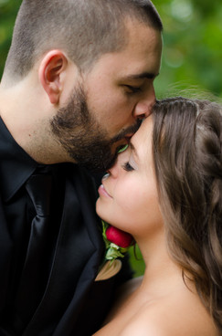 groom kissing bride on head