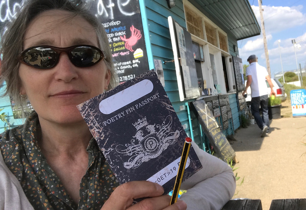A peddling poet showing off her recently stamped poetry passport at The Glorius Oyster, Instow.