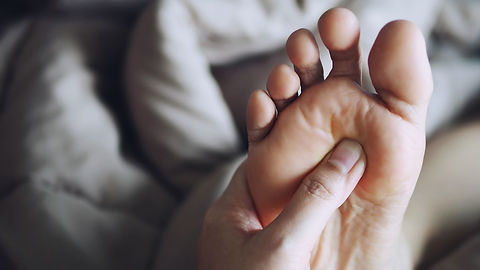 People giving a foot reflexology treatme