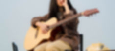 woman-holding-guitar-while-sitting-21180