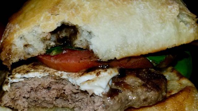 A bite from the birdger with black garlic, mozzarella, and spinach on a ciabatta.