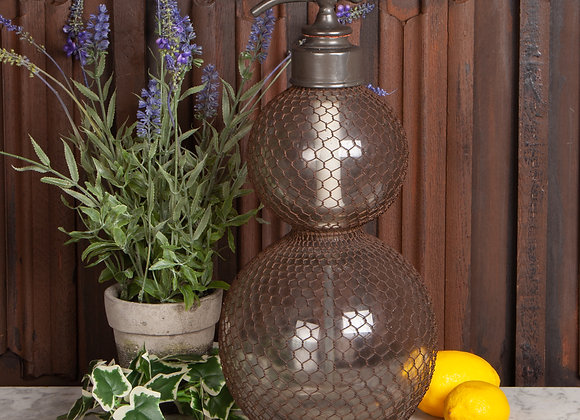 A Large Mesh Covered Soda Syphon
