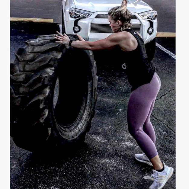 Ripped customers flipping a large tire in the fron parking lot at the fitness center