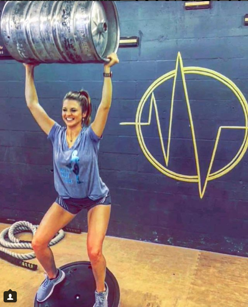 Customer in front of the gym logo while holding empty keg over heard