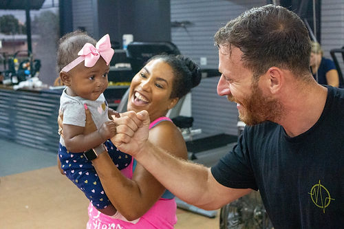 Gym owner giving a fist bump to a toddler while mother smiles