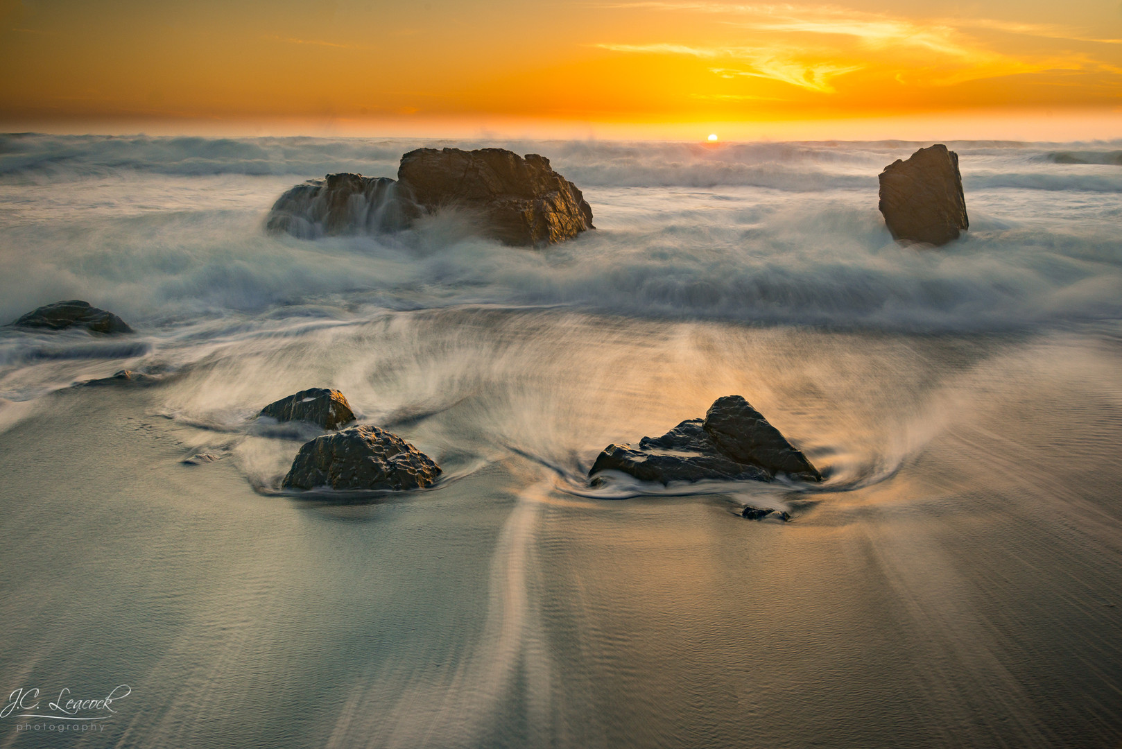 Surf amongst the rocks, at sunset, Westport, California