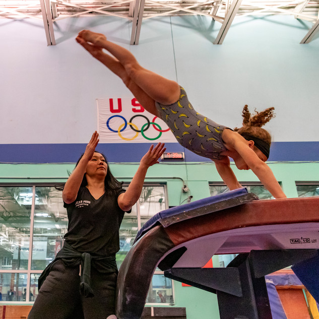 Coach Soomi Kim spots Sylvie Josse, age 7, over the vault during practice at Chelsea Piers Field House on March 16, 2018.