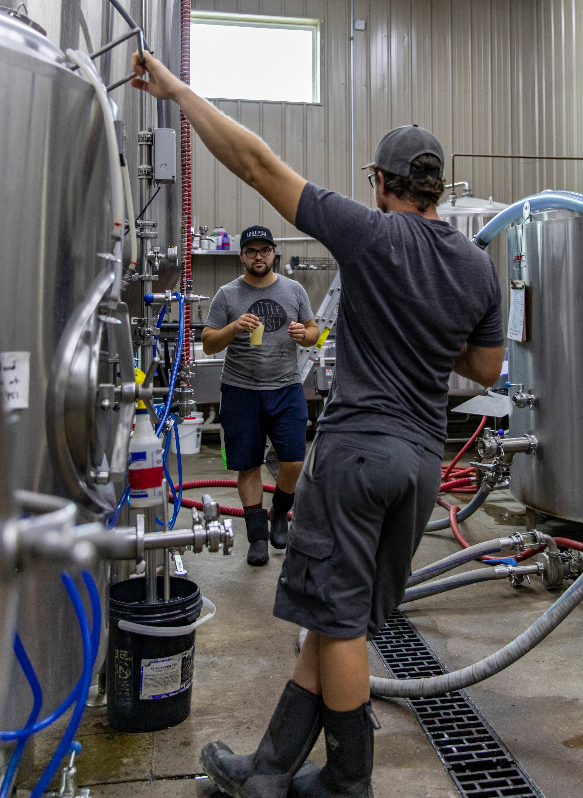 Front to back, Sean White and Tim Wasserman try a beer from the pot to see if it is ready to start to keg and package on October 10, 2018.