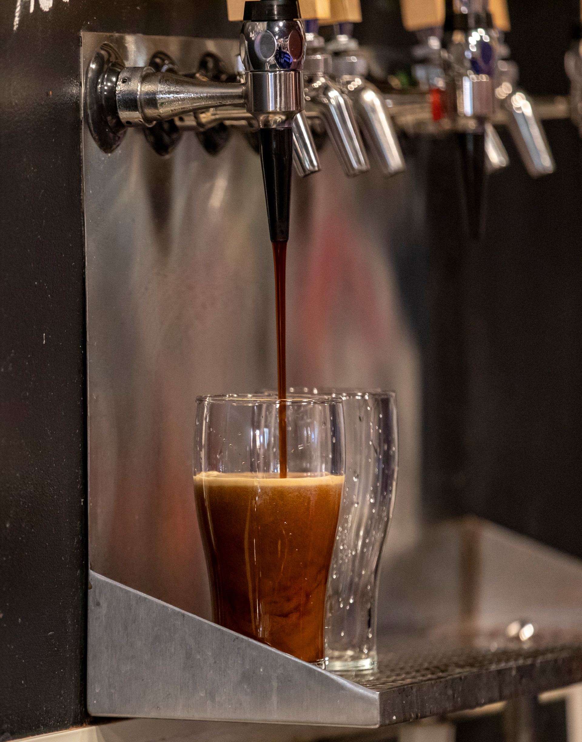 A beer sits under the tap in Little Fish's taproom late during Homecoming Weekend on October 20, 2018. Homecoming Weekend serves as a busy weekend for the taproom for alumni that don't want to be bothered by the bars lining Court St.