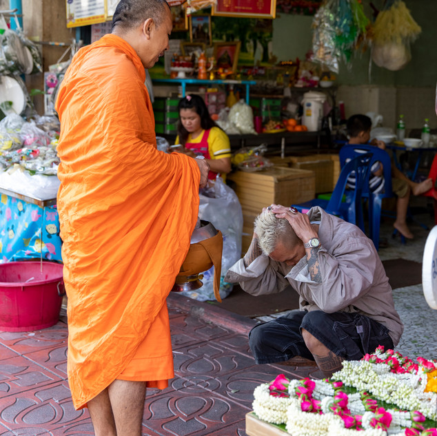 A shop owner is blessed by a monk after he made an offering to the monk that he can take back to his monestary early in the morning in Bangkok, Thailand.