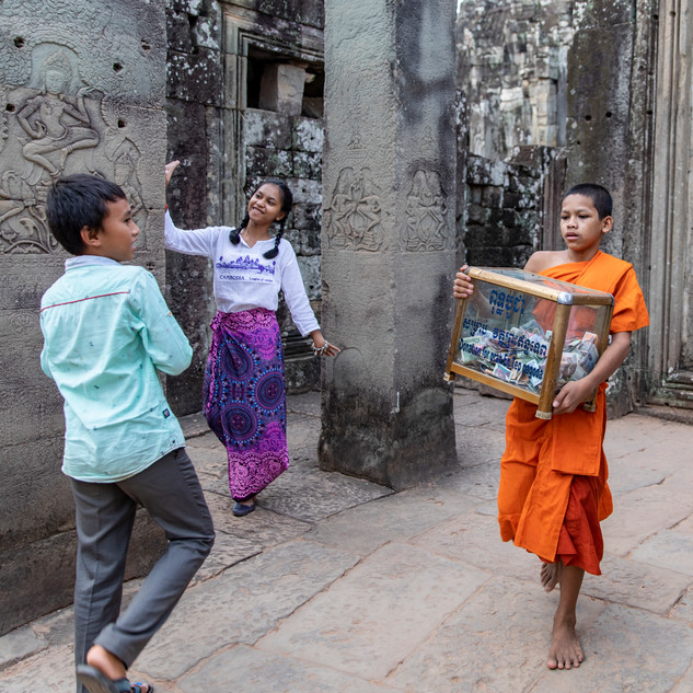 A child monk collects the donations by tourists while local kids pose for tourists at Bayon Temple, Cambodia after the temple had officially closed.