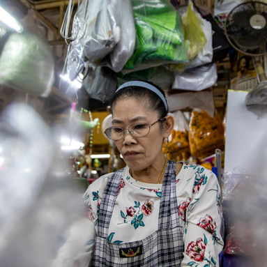A market shop owner packages flower bundles early in the morning in Bangkok, Thailand.