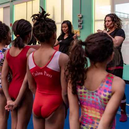 Right to left, Coach Soomi Kim and Coach Desiree Sanchez work with Level 6 gymnasts at Chelsea Piers Field House on March 16, 2018.