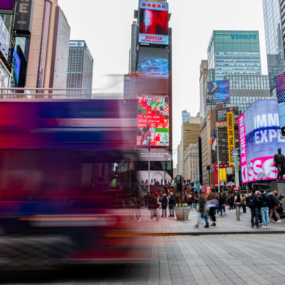 A double decker tour bus passes Times Square as it runs it route early in the morning on April 1, 2018.