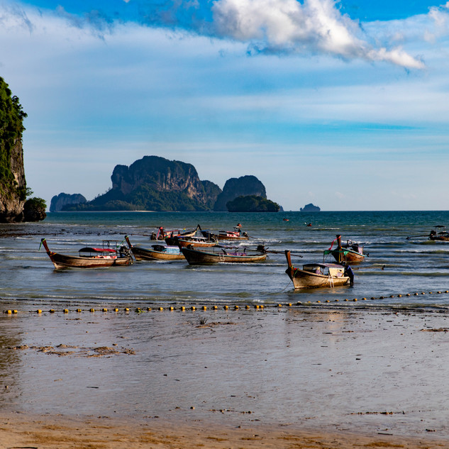 Local long boats docked on the shore of Krabi, Thailand before sunset.