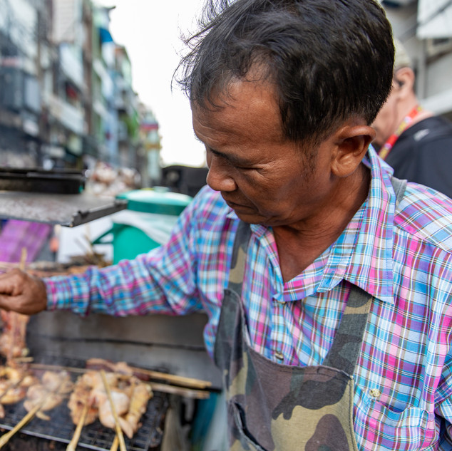 A local food vendor cooks up chicken and fish on his mobile cart in Bangkok, Thailand. Vendors like him stroll along the streets to cater to all of his customers and bringing the food to them.