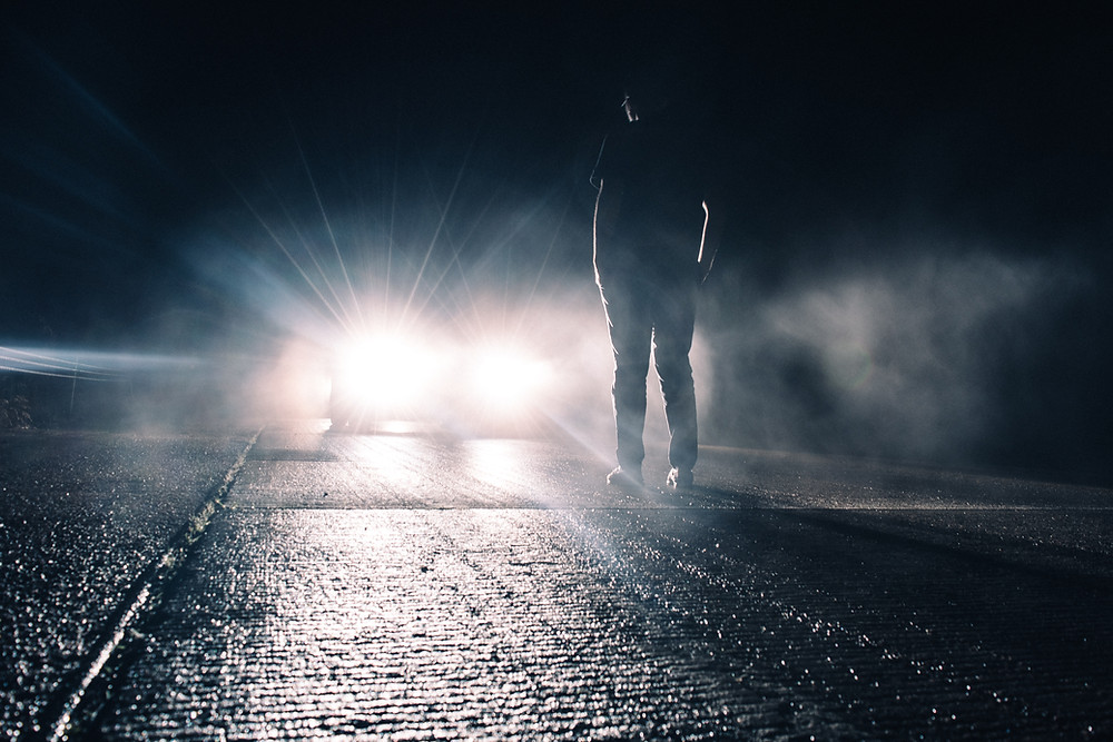 On a wet dark road with the image of a man standing in the middle of the road as a car with headlights ablaze approaches