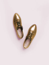 An empty gold shiny pair of shoes with black laces