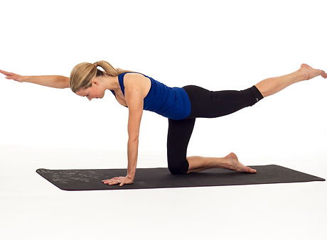 A woman performs a bird-dog rehabilitative exercise on a yoga mat.