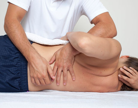 Ottawa Chiropractor performing sidelying spinal manipulation to a patient's lower back.