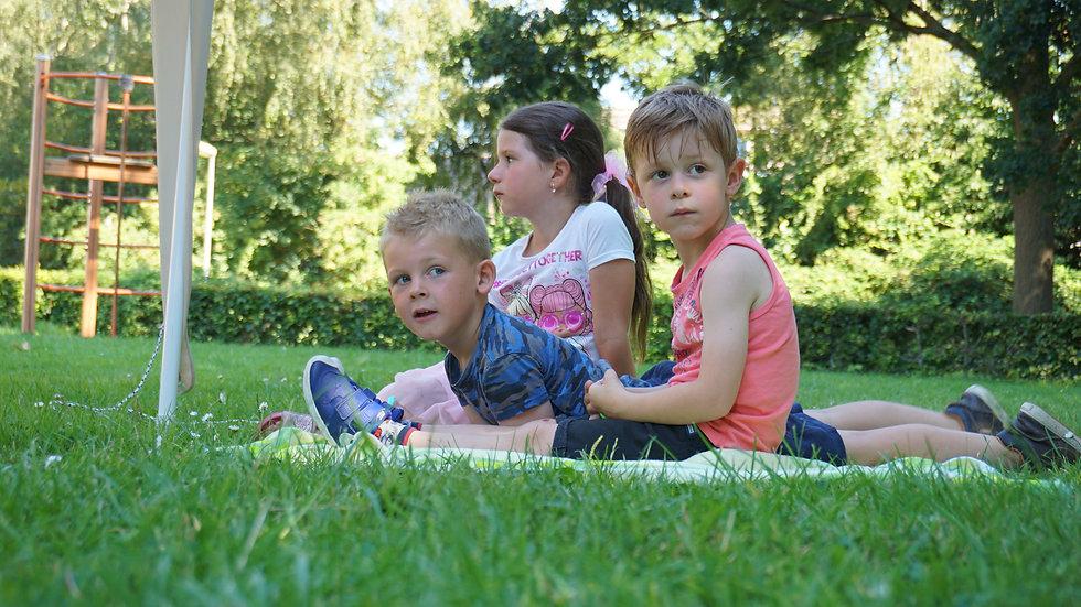 Twee jongens en één meisje zittend/liggend op het gras
