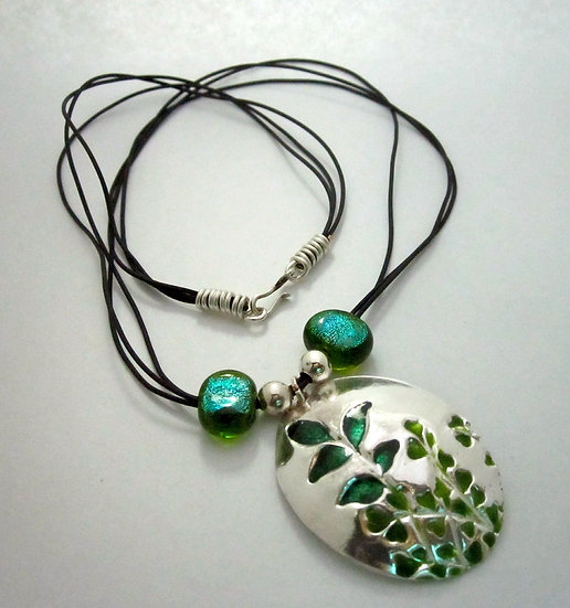 Enameled Leaves Imbedded In An Oval Pendant.