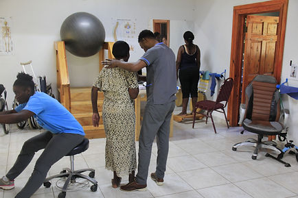 A physical therapist walking with a patient at Bethesda Medical Center in Haiti