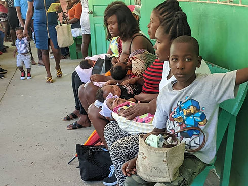 A boy sits on the end of a bench, looking at the camera.  beside his are four mothers with their babies on their laps as they wait to see the nurse at Bethesda Medical Center in Haiti