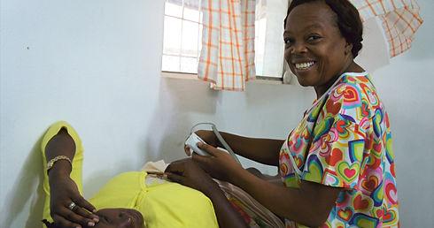 A nurse performing an ultrasound on a pregnant woman's abdomen at Bethesda Medical Center