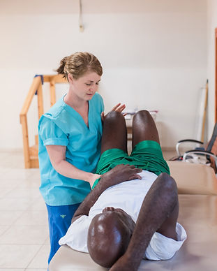 Physio working with a man's knee at Bethesda Medical Center in Haiti