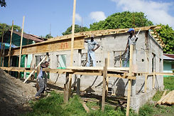 Men standing on wooden scaffolding in front of a building they are buuilding at Bethesda Medical Center in Haiti