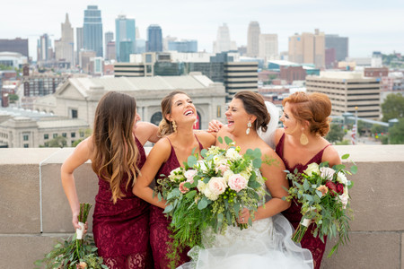 bridemaids laughing with kansas city skyline in background