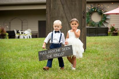 ring bearer and flower girl holding sign at wedding