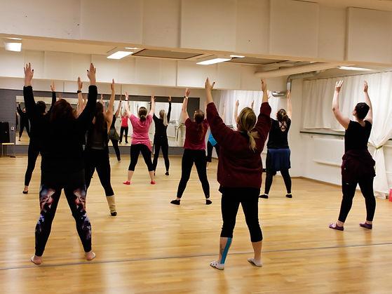 Naiset tanssisalissa ovat nostaneet kätensä ylös tanssitunnin alkulämmittelyssä.