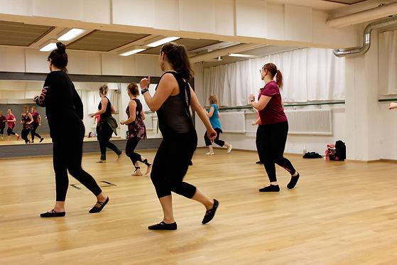 Naiset tanssisalissa liikkuvat salsan tahtiin.