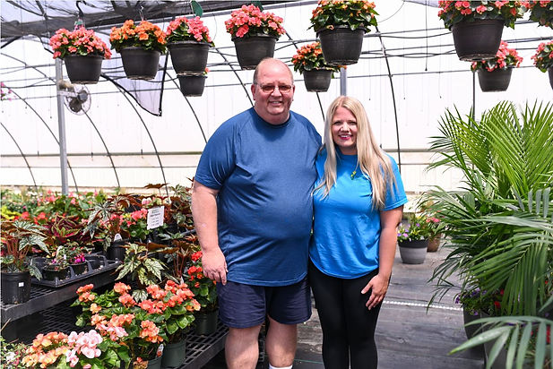 a farther and daughter standing in a greenhouse
