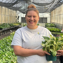 A woman holding a plant in a greenhouse