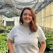 A woman standing in a greenhouse