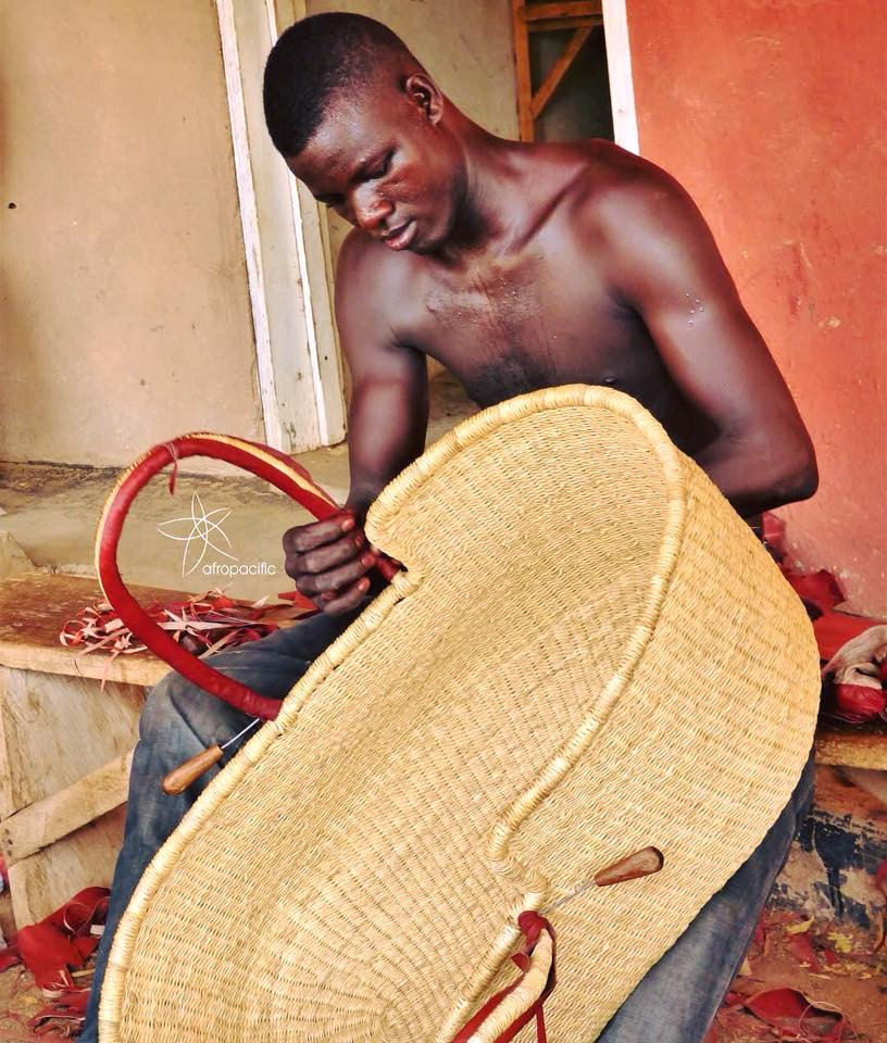 A Ghanaian weaver, finishing the leather handles on a Bilia Moses Basket
