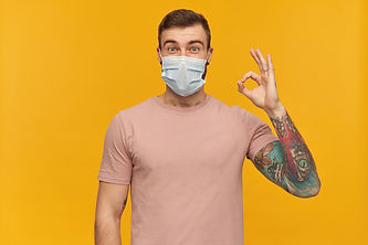 excited-tattooed-young-man-in-pink-tshirt-and-virus-protective-mask-on-face-against-corona