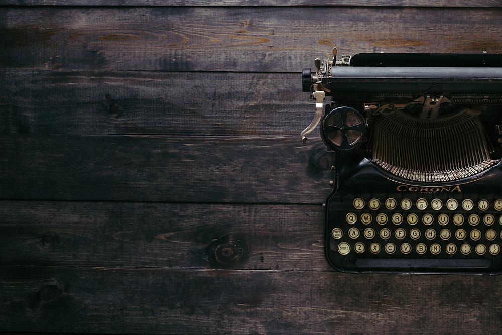 Black type writer on dark wood table