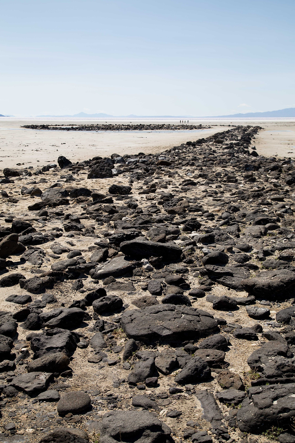 Large black basalt rocks make up the coil of the Spiral Jetty on the shore of the Great Salt Lake in Utah