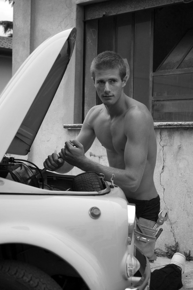 Alberto Carniel posing like a mechanic who is fixing FIAT 500's engine