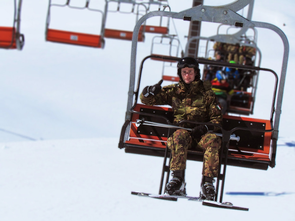 Skiing Italian Red Cross army soldier on a chairlift
